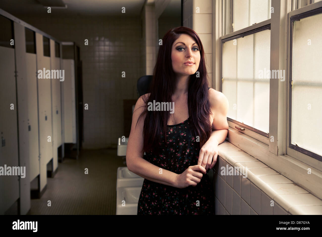 Woman standing next to window in public bathroom - Stock Image
