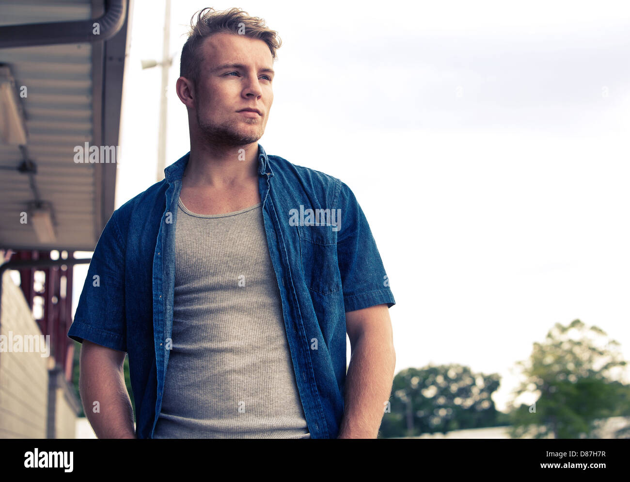 Man standing outside with blue shirt against sky - Stock Image