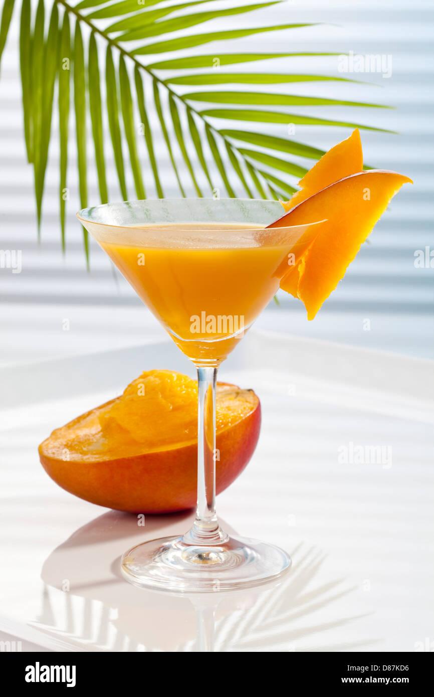 Glass of mango juice besides mango - Stock Image