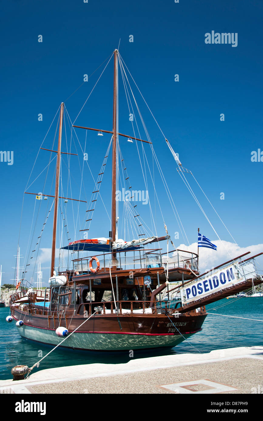 Tourism beautiful wooden sailing boat names Poseidon in the harbour of Kos - Dodecanese islands, Greece - Stock Image