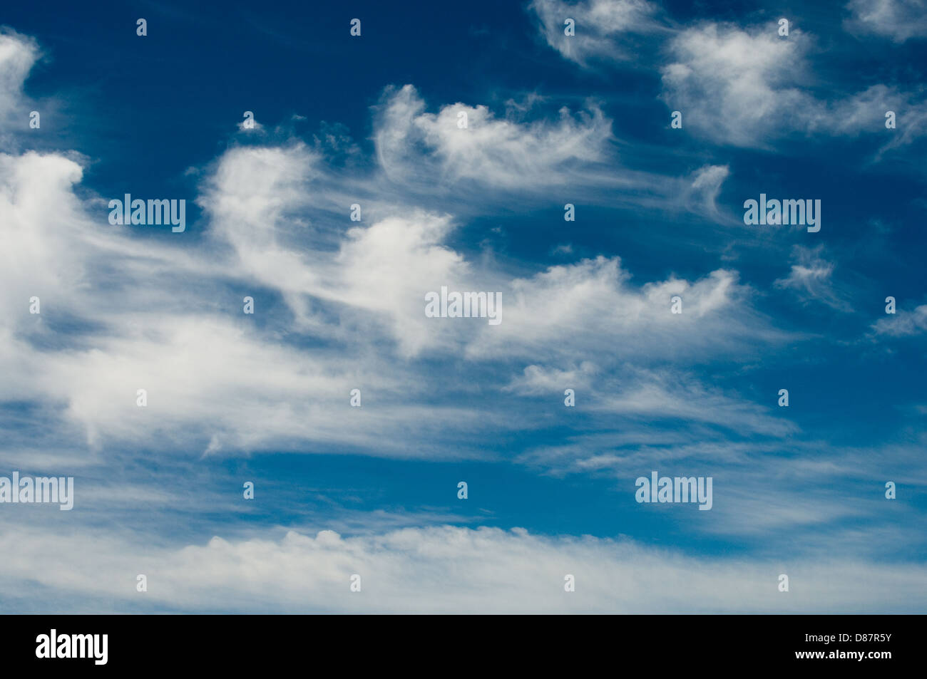 White fluffy clouds are blown across a blue sky on the Maltese coast - Stock Image