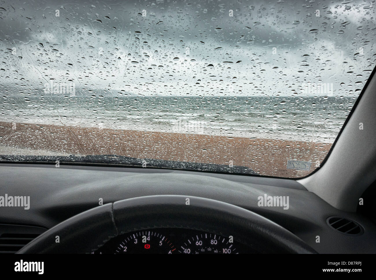 British seaside beach on a rainy day through the car windshield / windscreen - Stock Image