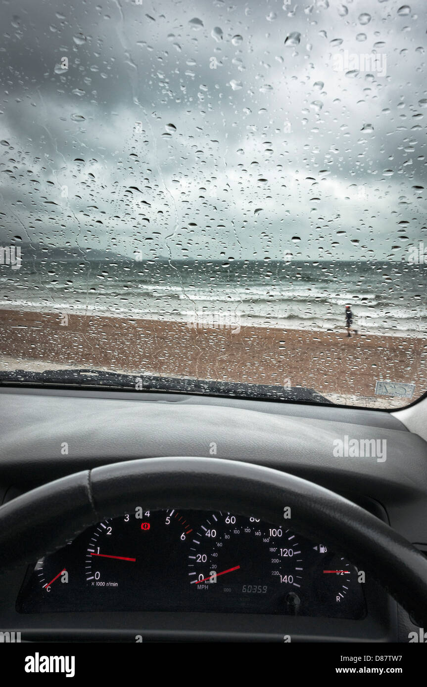 UK south coast beach through a car windscreen on a rainy day in Spring/Summer with a man running - Stock Image