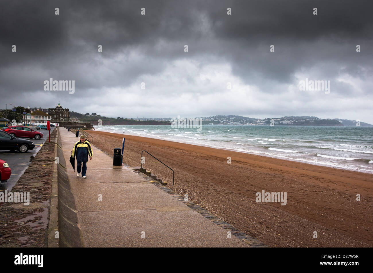 Man walking at the edge of Paignton beach in a rain storm on a rainy day, England, UK - Stock Image