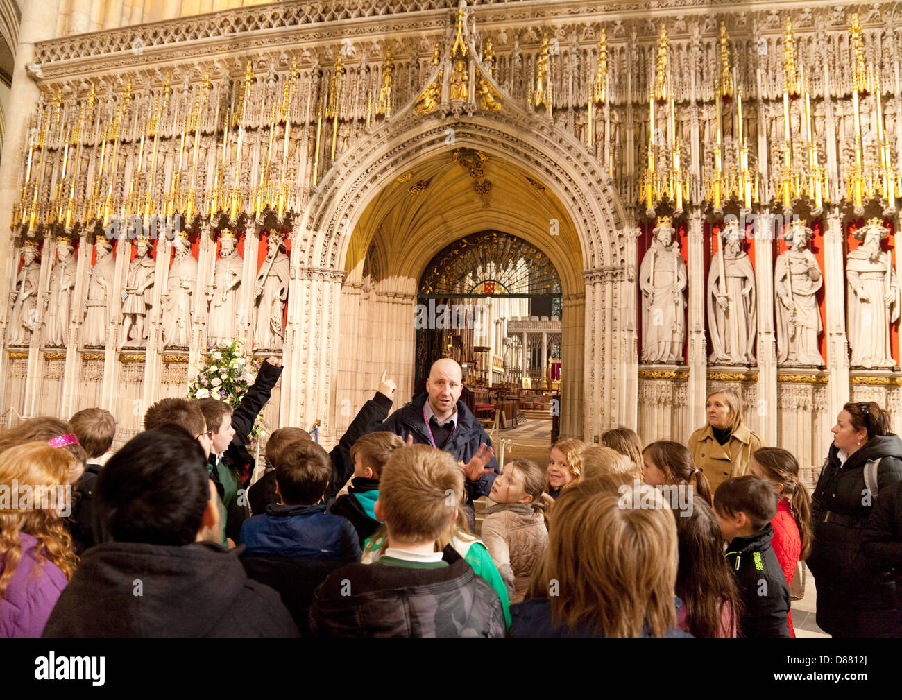 Children and their teacher on school trip guided tour of York Minster cathedral, York, Yorkshire UK - Stock Image