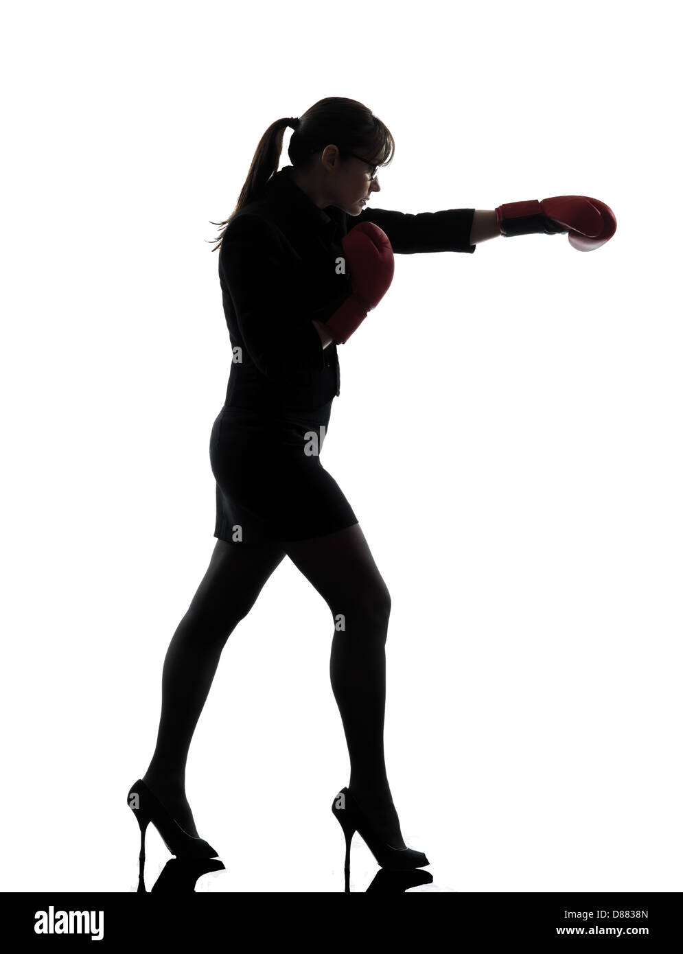 one business woman punching with boxing gloves silhouette studio isolated on white background - Stock Image
