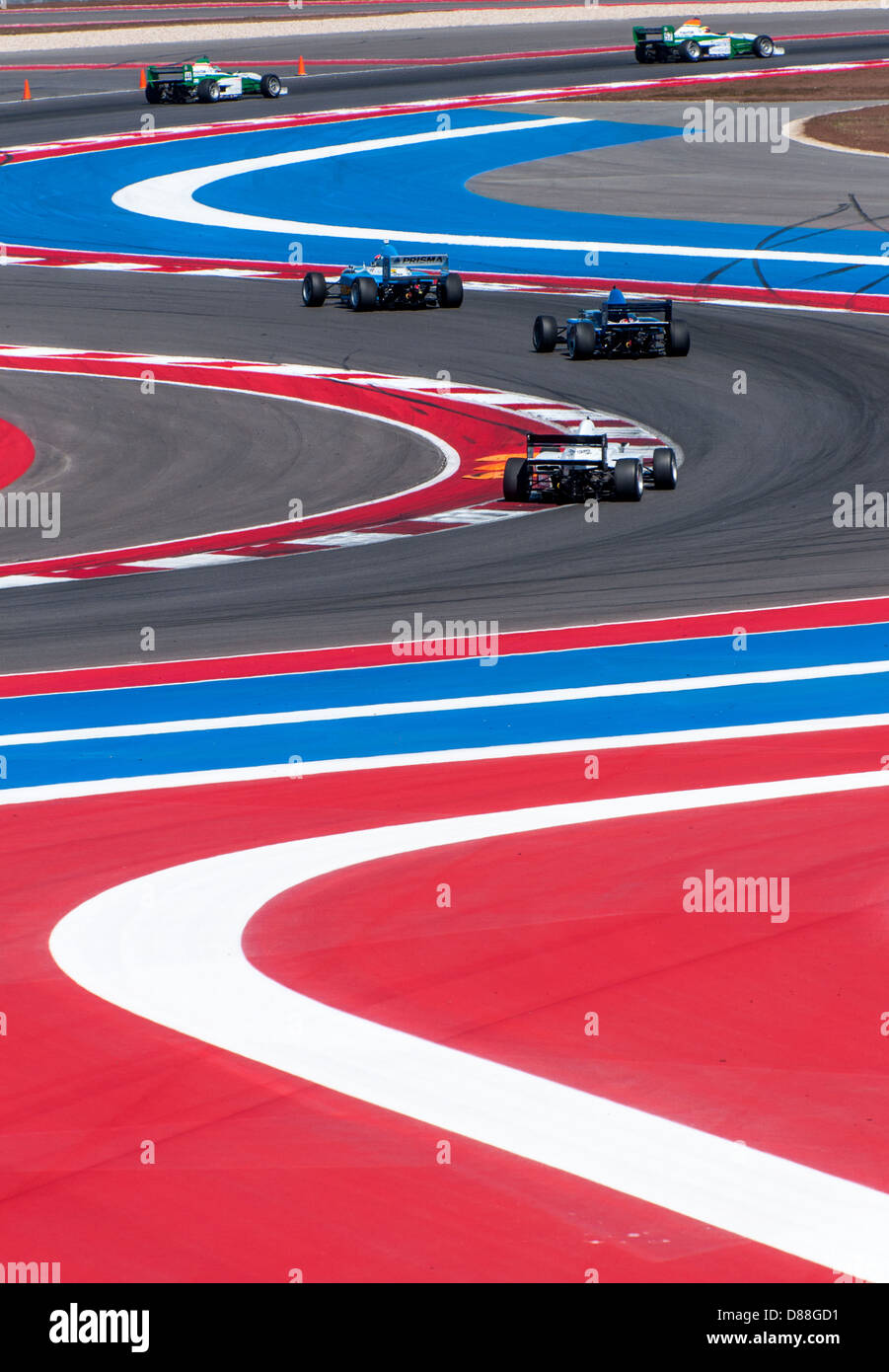 Several Pro Mazda Series racing cars negotiate the S-curves at Circuit of the Americas, Austin, Texas. - Stock Image