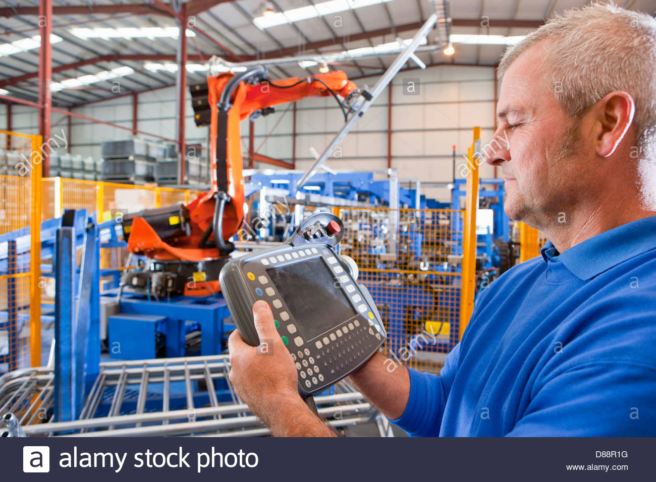 Close up of worker controlling robotic machinery lifting steel fencing on production line in manufacturing plant - Stock Image