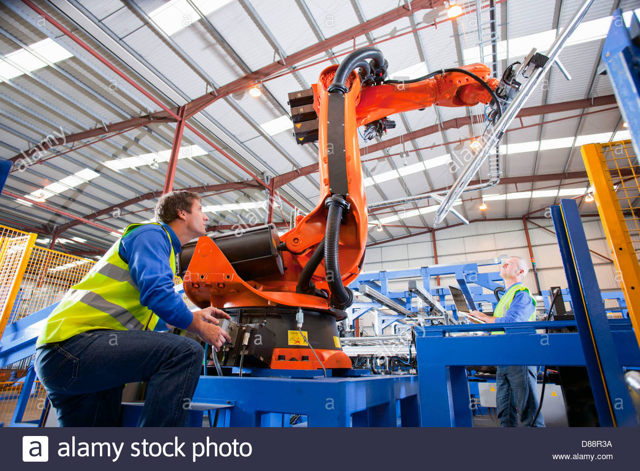 Technician controlling robotic machinery lifting steel fencing on production line in manufacturing plant - Stock Image