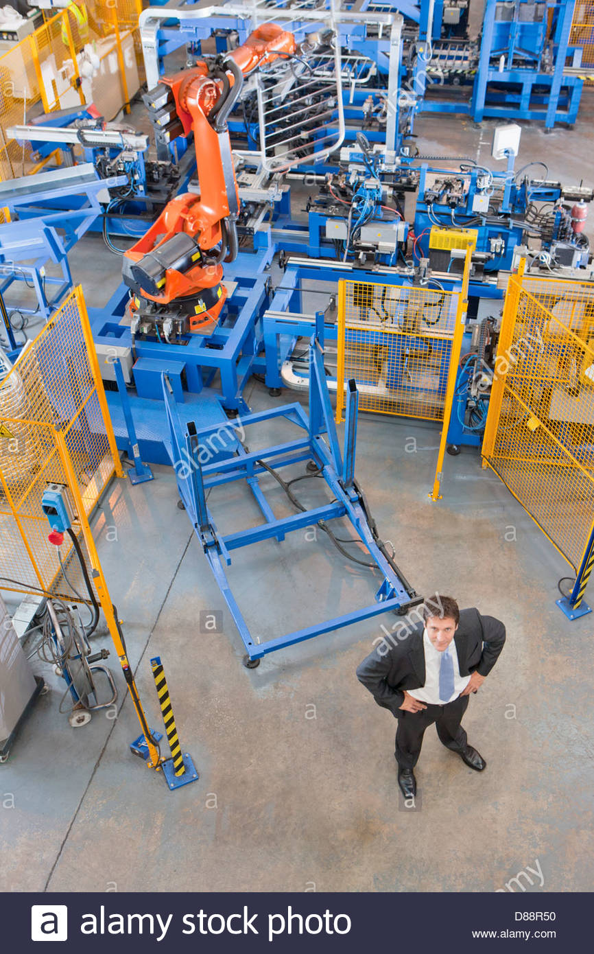 Portrait of confident businessman in front of robotic machinery lifting steel fencing on production line in manufacturing - Stock Image