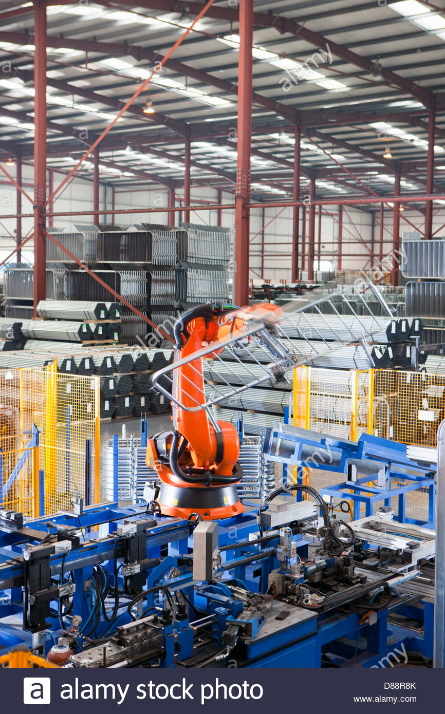 Robotic machinery lifting steel fencing on production line in manufacturing plant - Stock Image