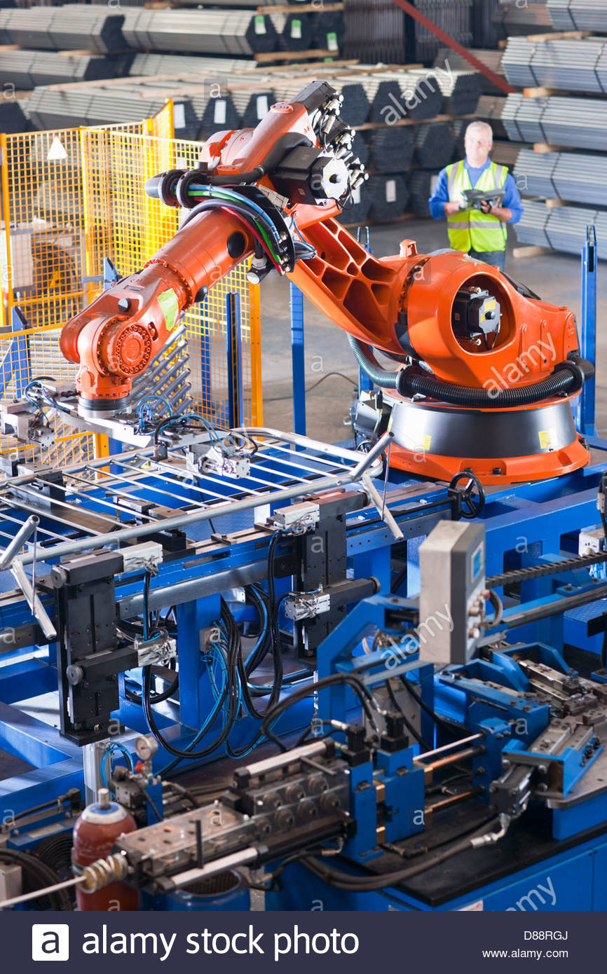 Worker controlling robotic machinery lifting steel fencing on production line in manufacturing plant Stock Photo