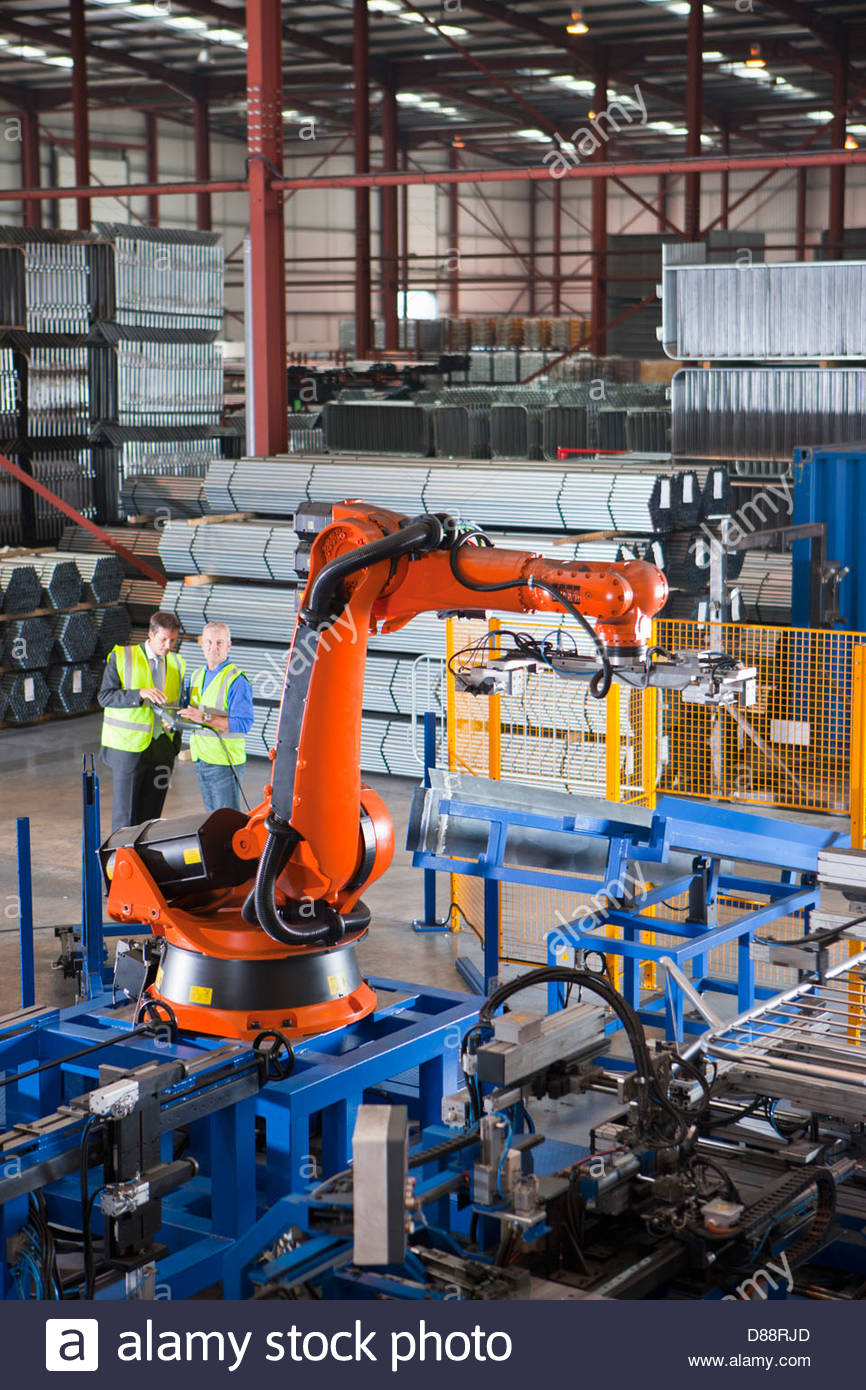 Businessman and worker controlling robotic machinery lifting steel fencing on production line in manufacturing plant - Stock Image