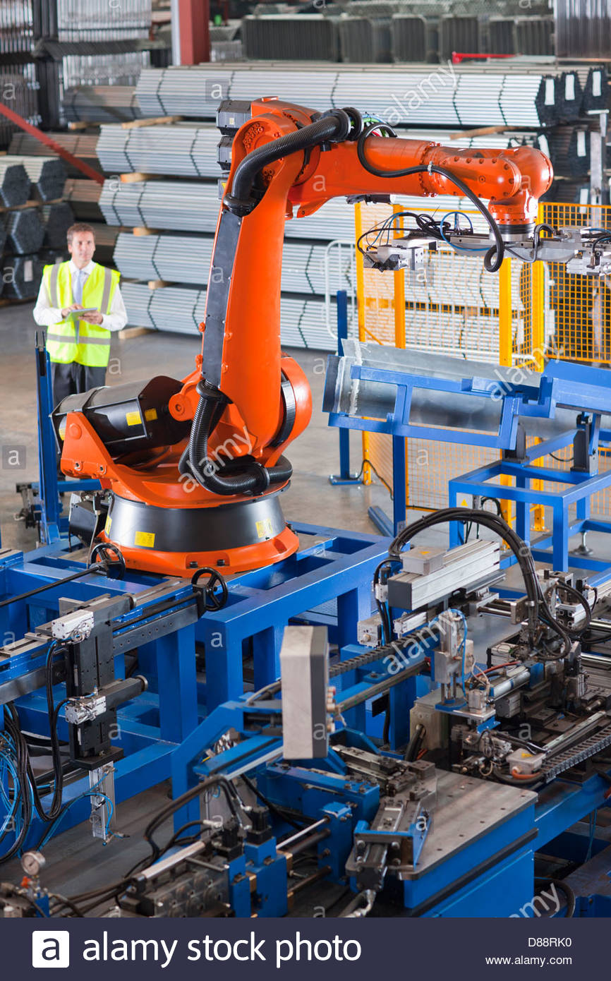 Businessman controlling robotic machinery lifting steel fencing on production line in manufacturing plant - Stock Image