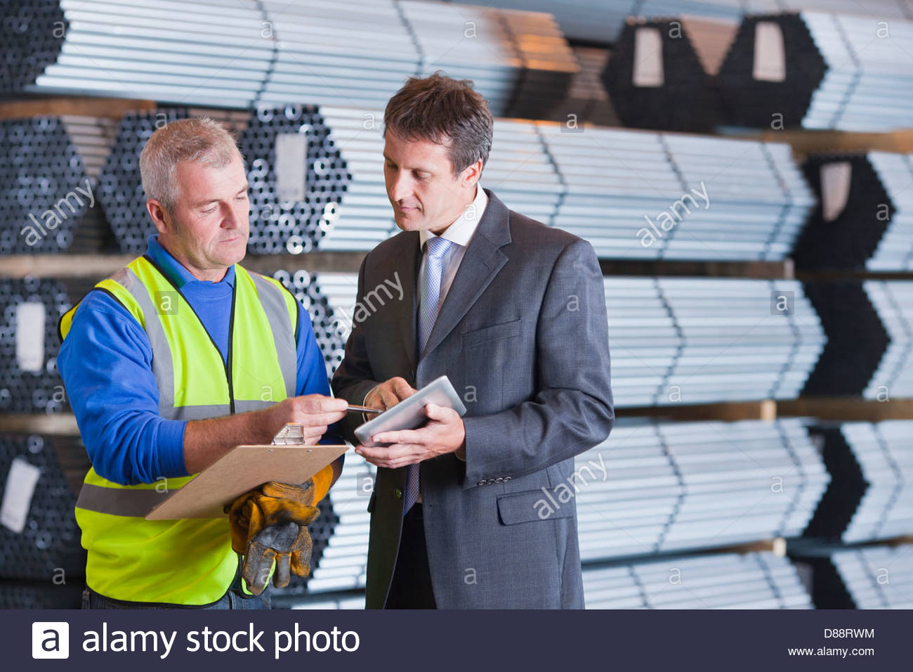 Businessman and worker with clipboard and digital tablet in front of steel tubing - Stock Image