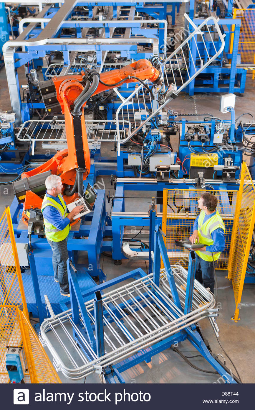 Workers watching robotic machinery lift steel fencing on production line in manufacturing plant - Stock Image
