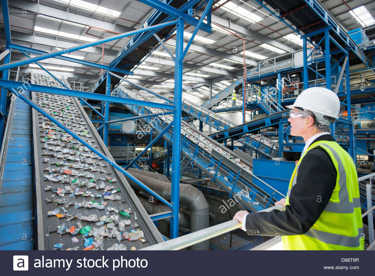Businessman watching plastic on conveyor belt in recycling plant - Stock Image