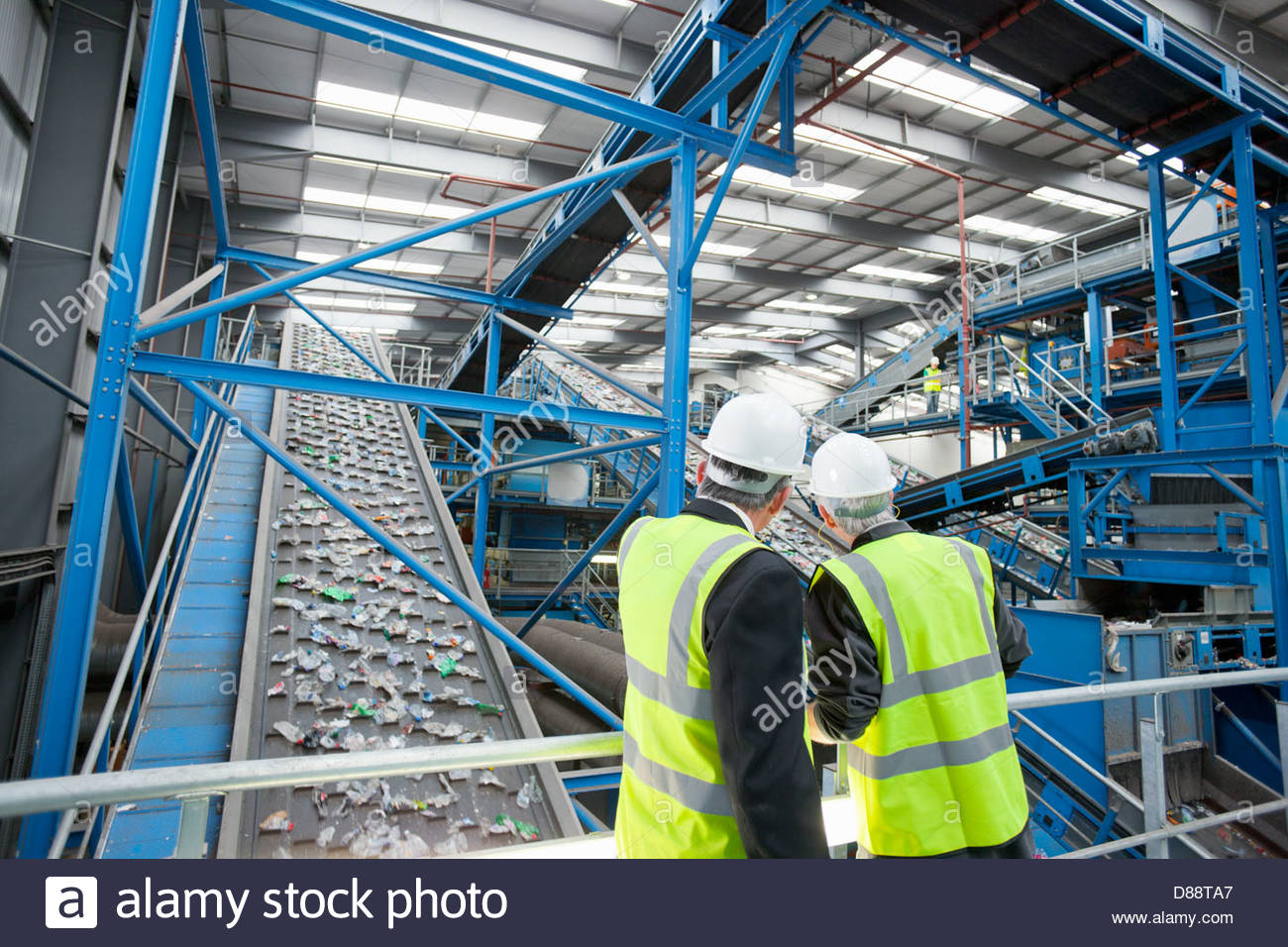 Businessmen watching plastic on conveyor belt in recycling plant - Stock Image