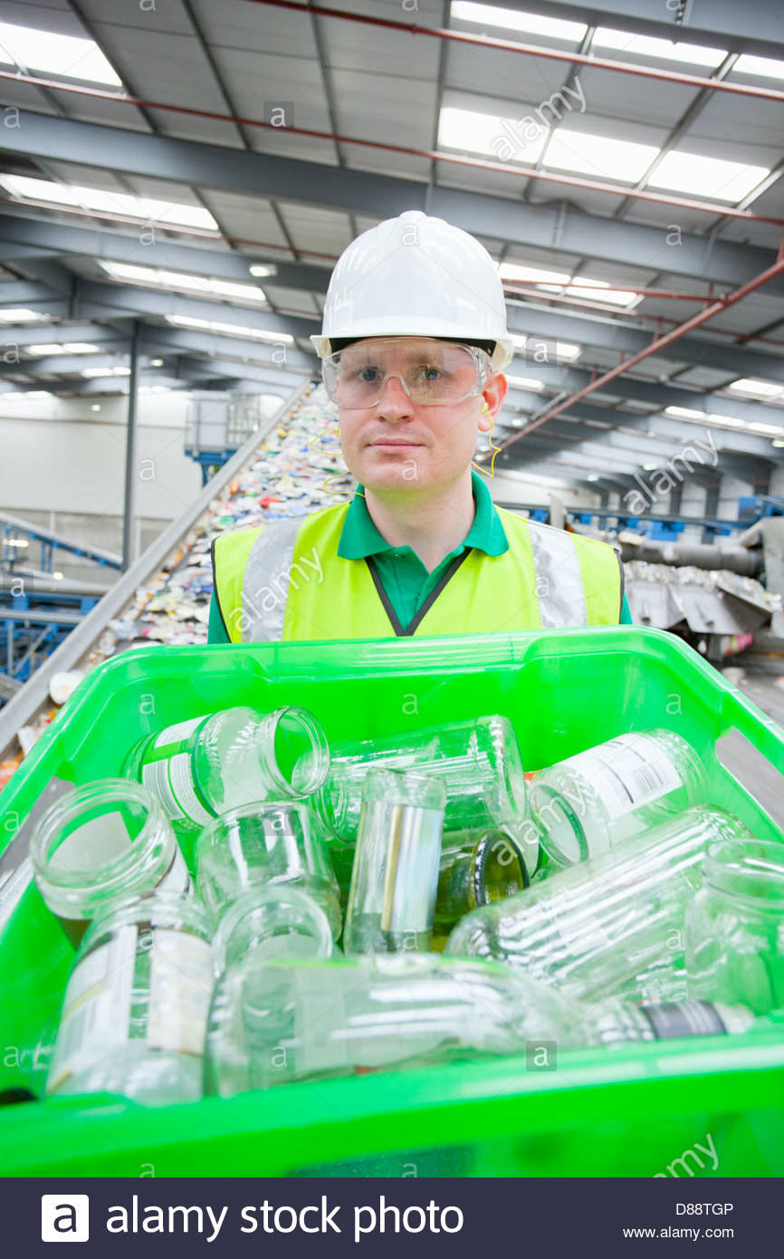 Portrait of worker holding bin with glass bottles in recycling plant - Stock Image