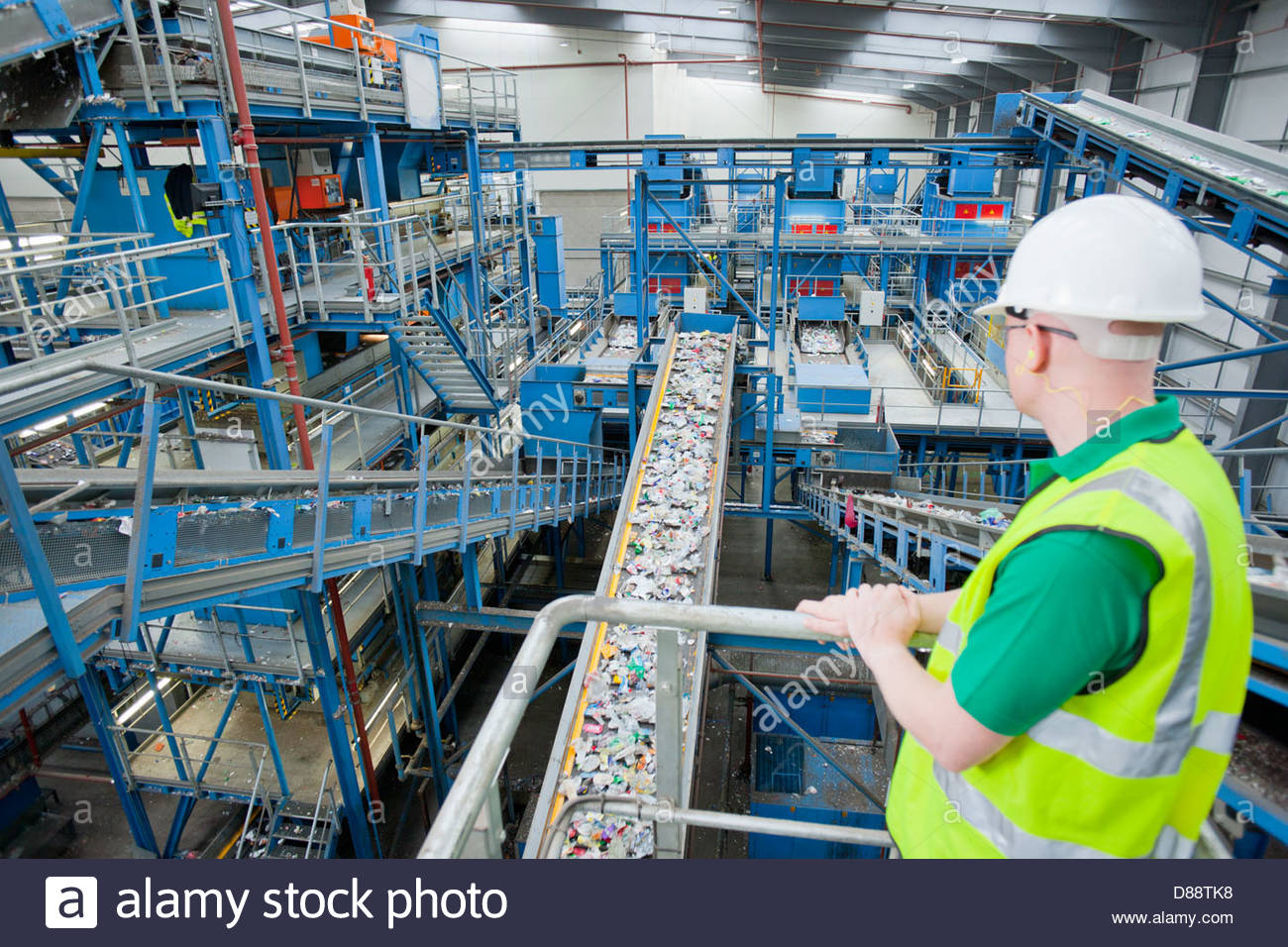 Worker watching plastic on conveyor belt in recycling plant - Stock Image