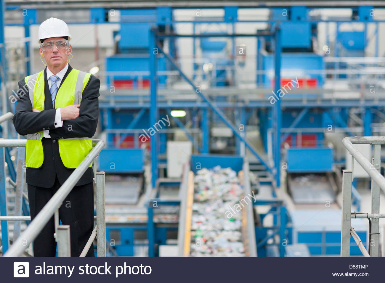 Portrait of serious businessman standing on platform above conveyor belt in recycling plant - Stock Image