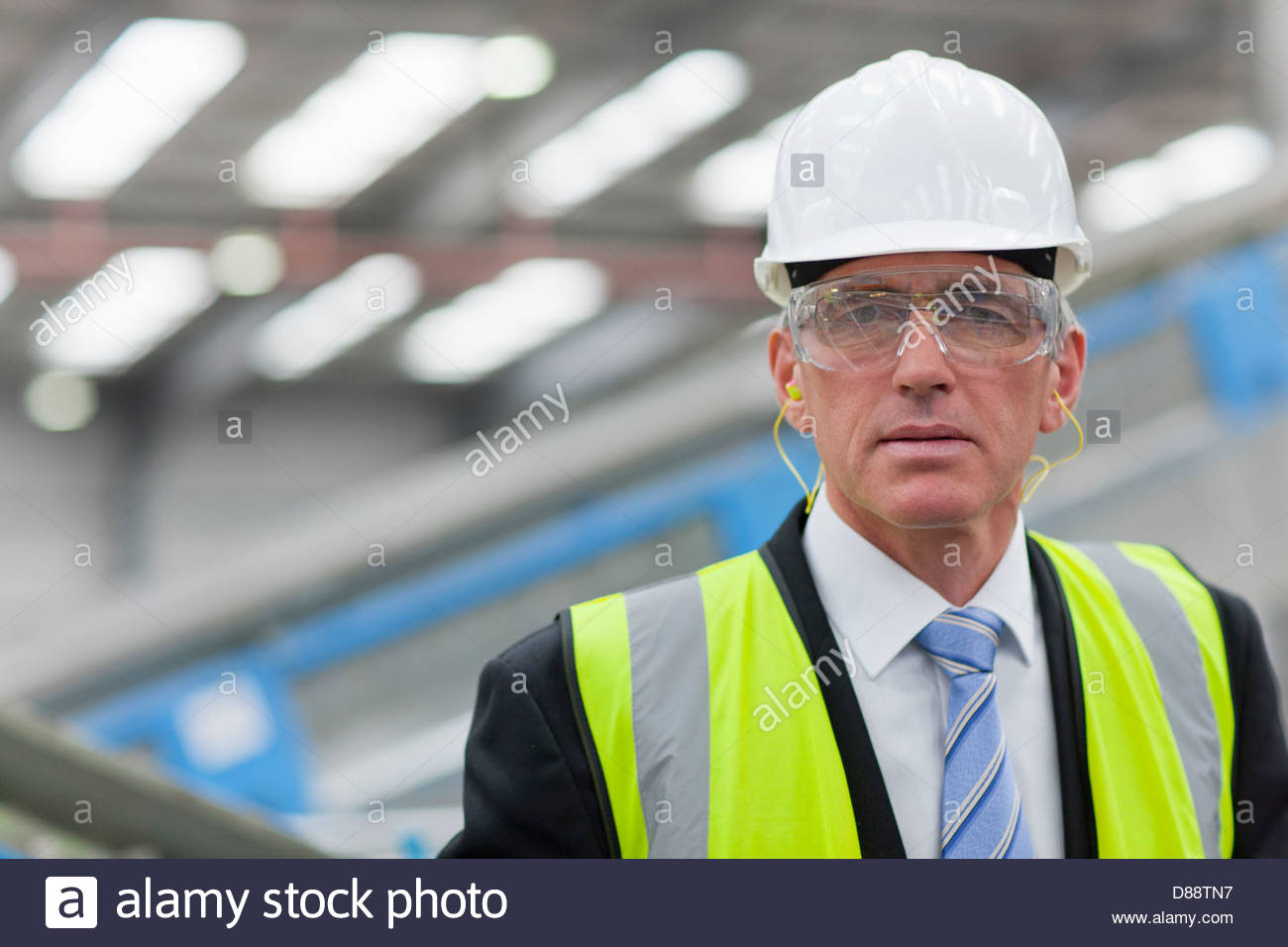 Close up portrait of serious businessman wearing hard-hat, goggles and reflector-vest in recycling plant - Stock Image