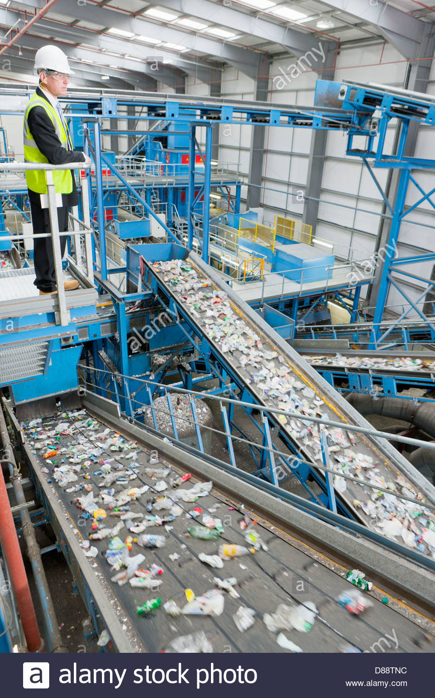 Businessman on platform above conveyor belts in recycling plant - Stock Image