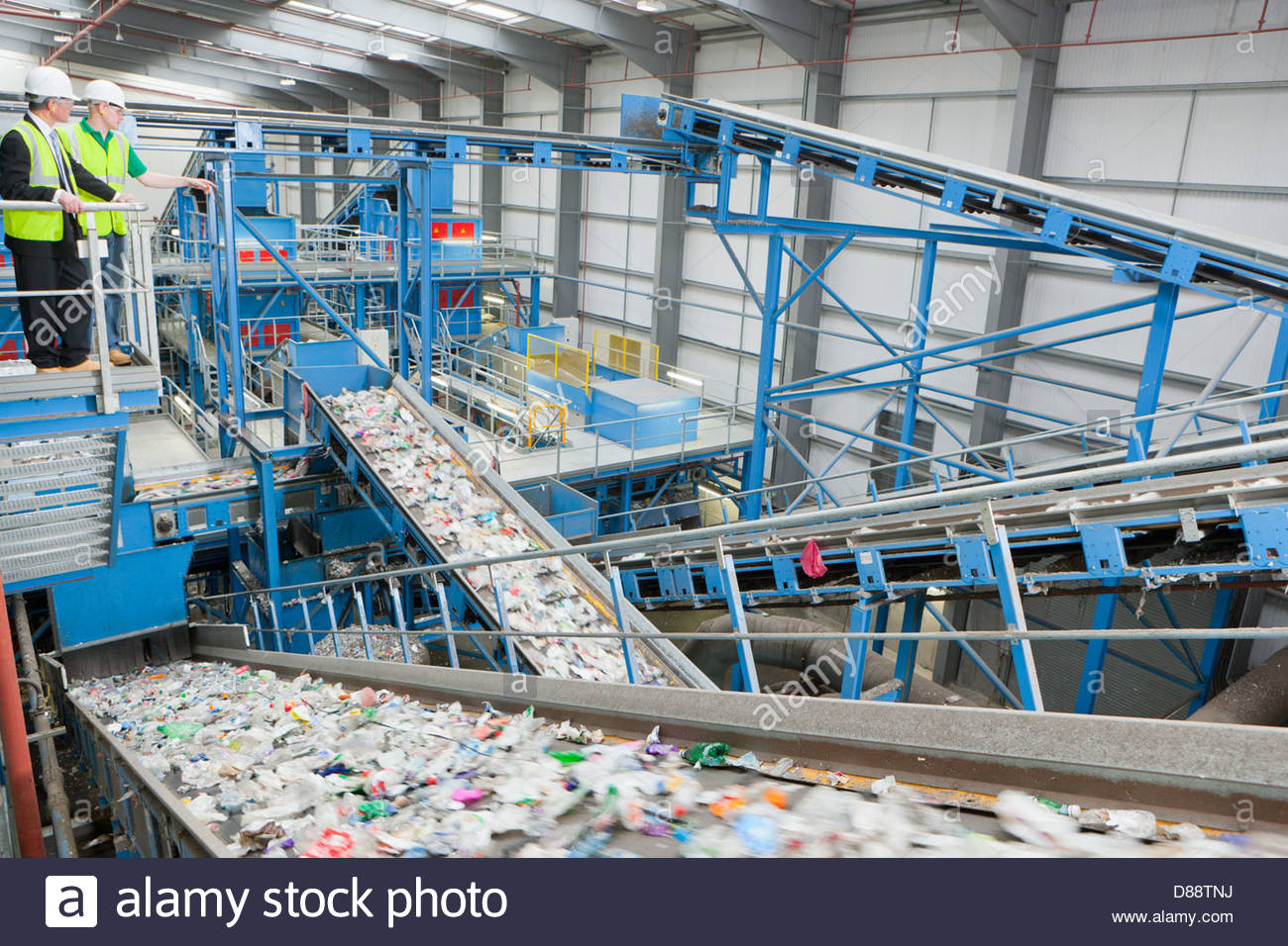 Businessman and worker on platform above conveyor belts in recycling plant - Stock Image