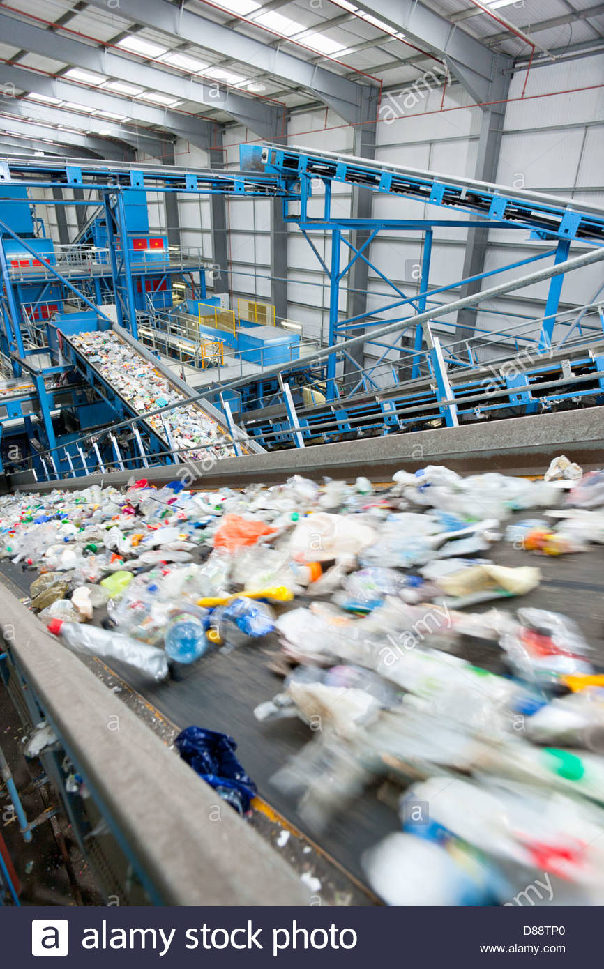 Plastic moving along conveyor belt in recycling plant - Stock Image