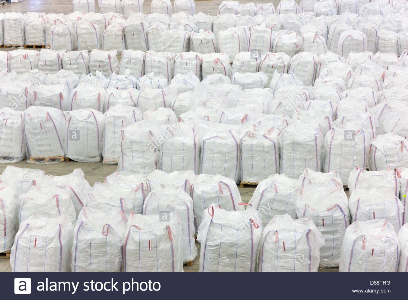 Large bags of recycled plastic pellets in warehouse - Stock Image