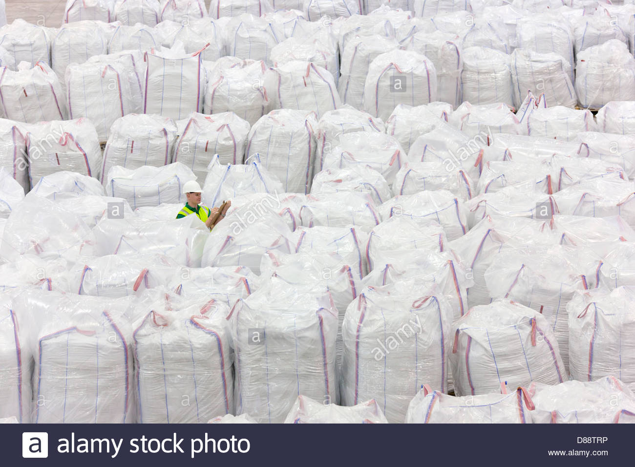 Worker among large bags of plastic pellets in warehouse - Stock Image