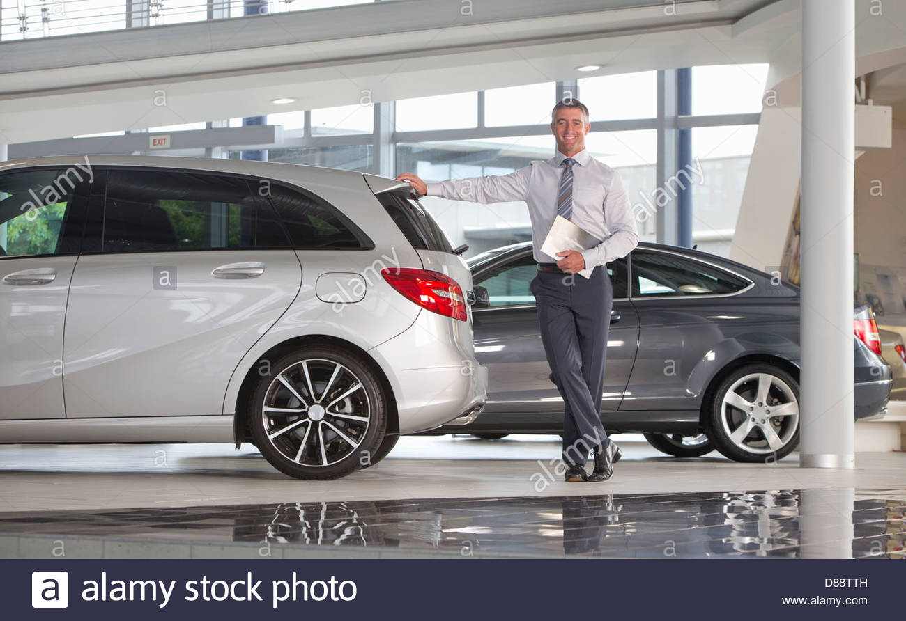 Portrait of smiling salesman holding brochure and leaning on car in car dealership showroom - Stock Image