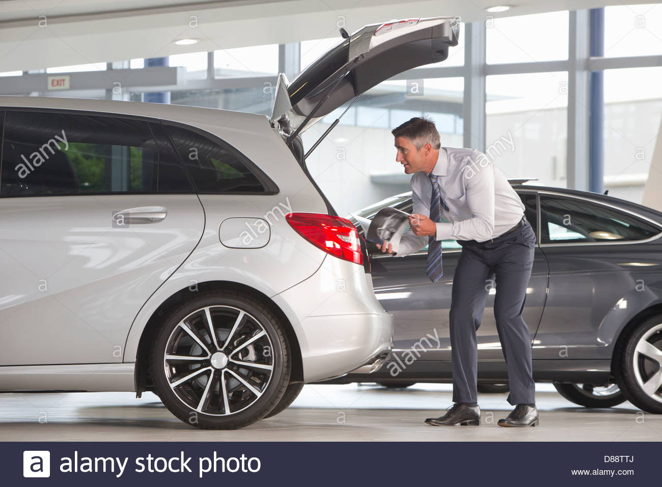 Man with brochure looking into hatchback of car in car dealership showroom - Stock Image