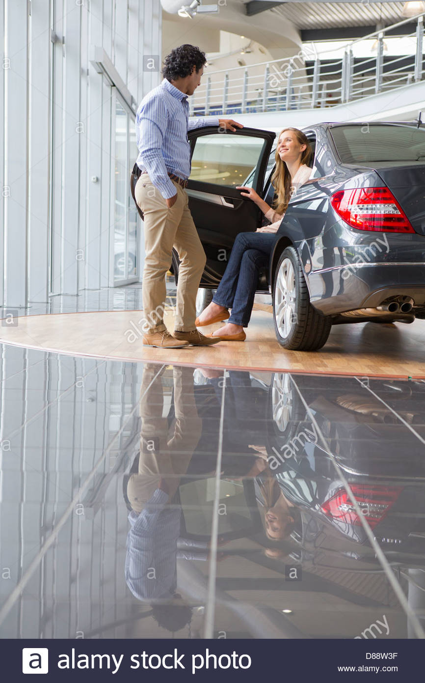 Couple looking at car in car dealership showroom - Stock Image