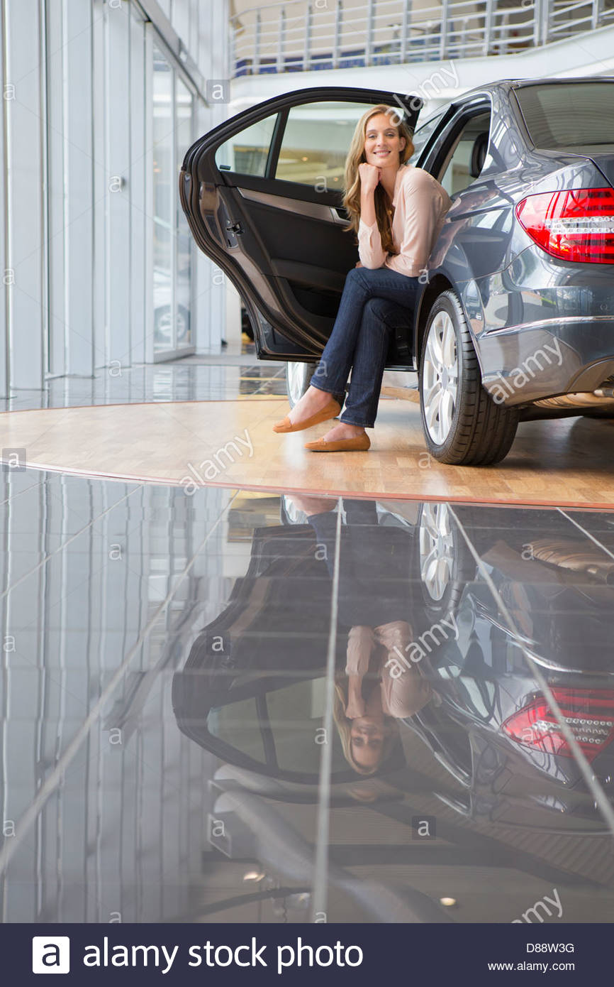 Portrait of smiling woman sitting in back seat of car in car dealership showroom - Stock Image