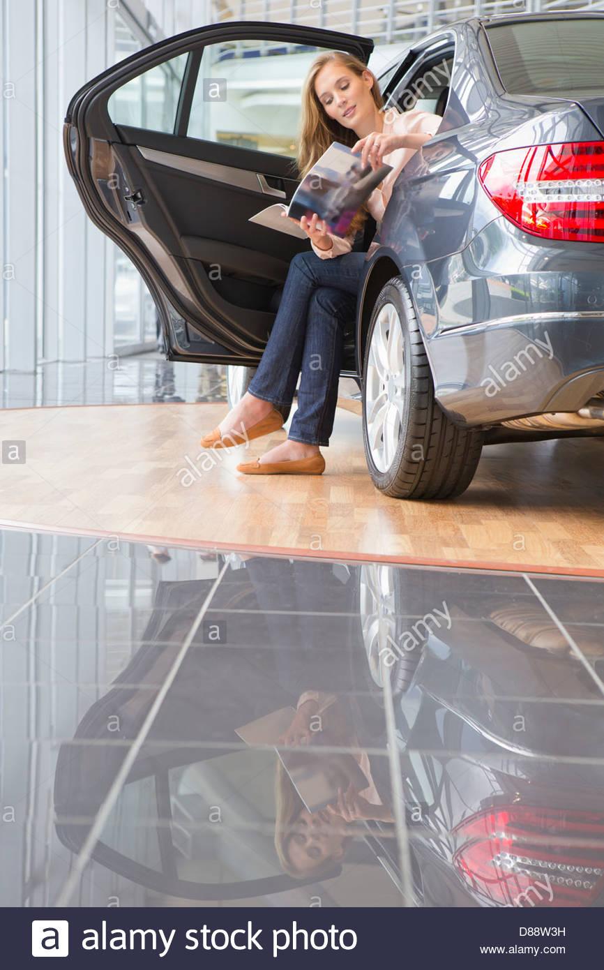 Woman looking at brochure in back seat of car in car dealership showroom - Stock Image