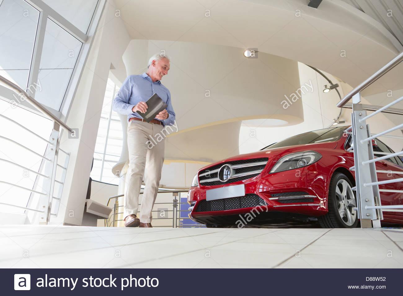 Man looking at car in car dealership showroom - Stock Image