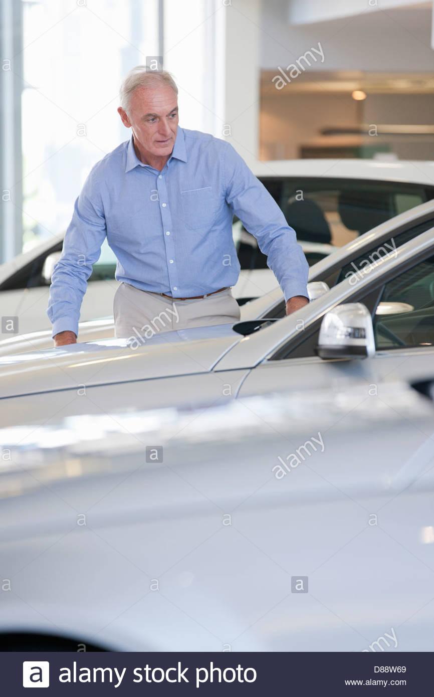 Customer looking at car in car dealership showroom - Stock Image