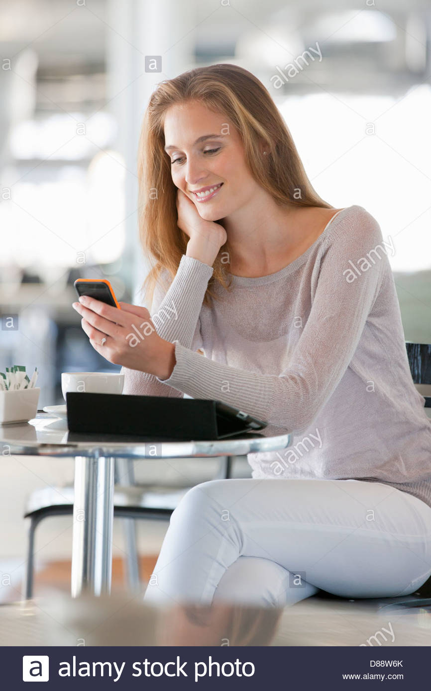 Woman checking cell phone at cafe table - Stock Image
