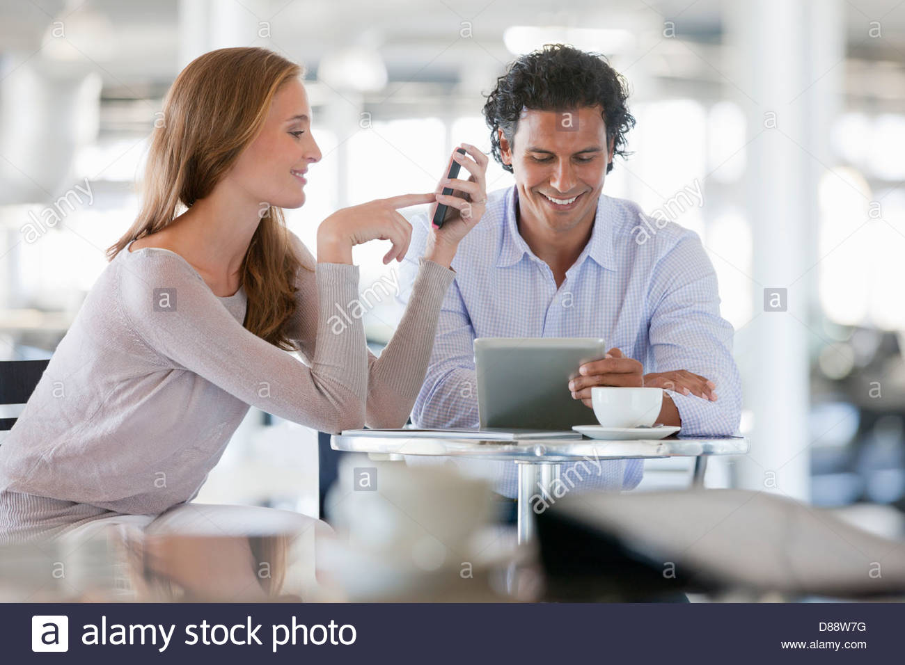 Couple using cell phone and digital tablet at cafe table - Stock Image