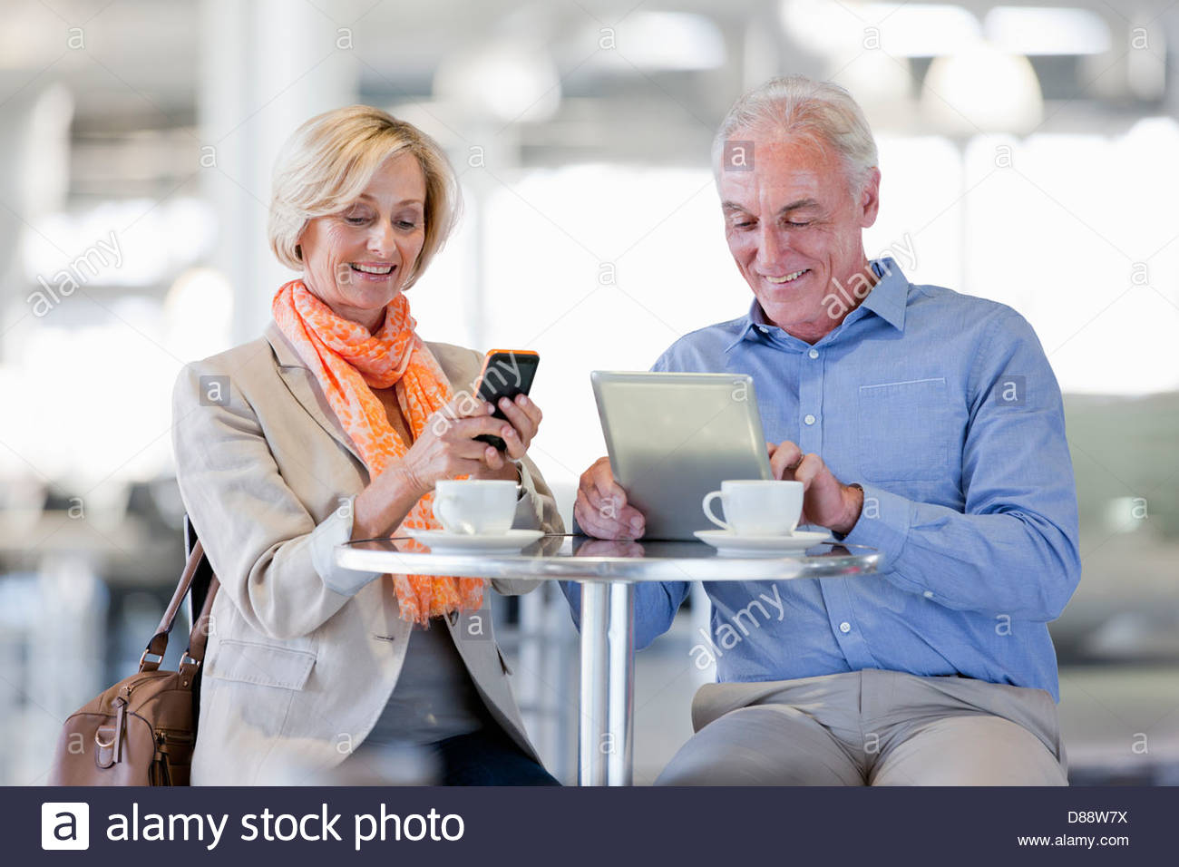 Smiling couple using cell phone and digital tablet at cafe table - Stock Image