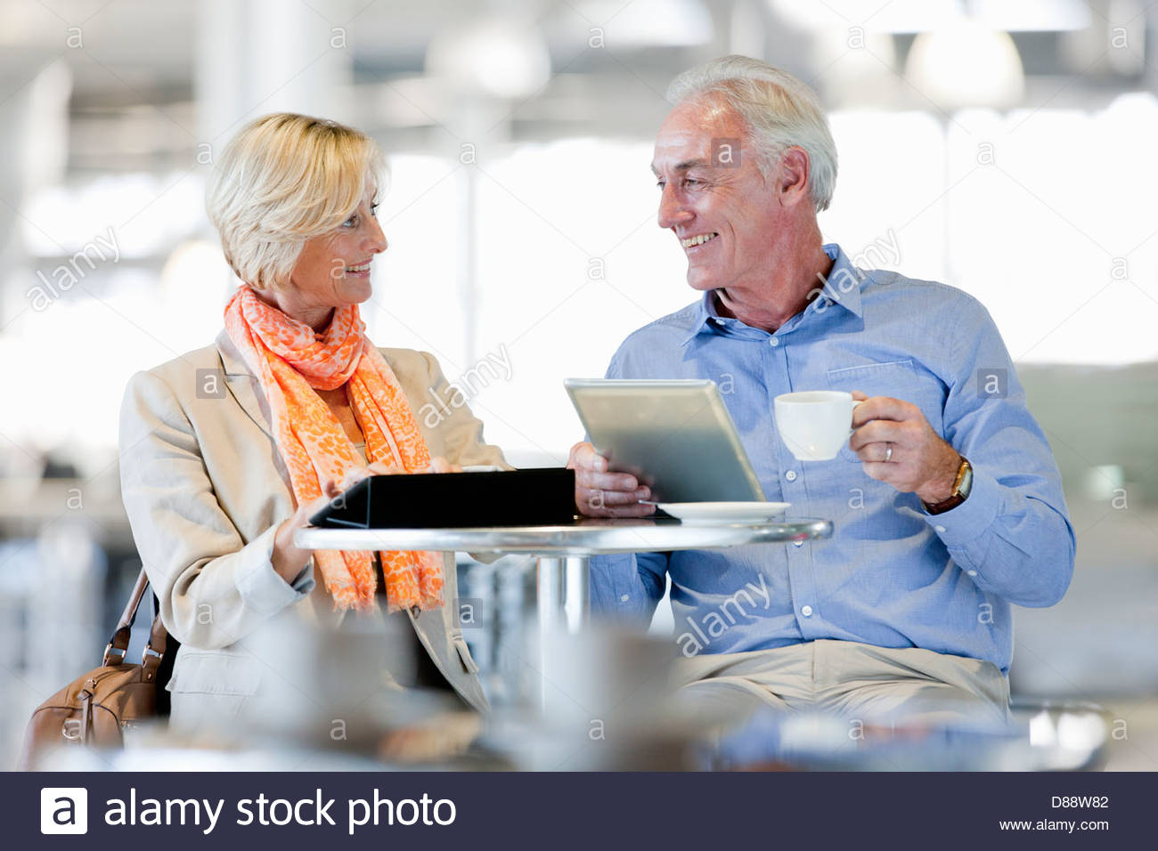 Smiling couple using digital tablets at cafe table Stock Photo