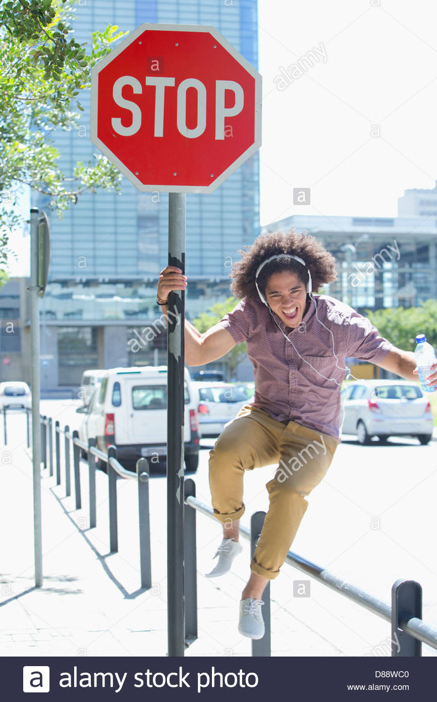 Portrait of enthusiastic young man listening to music on headphones against stop sign in city - Stock Image