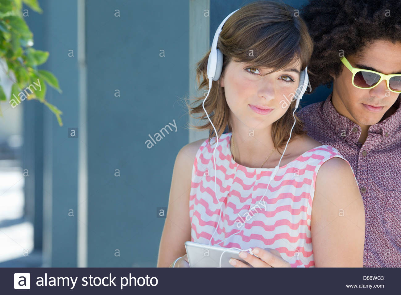 Portrait of young couple wearing headphones with digital tablet Stock Photo