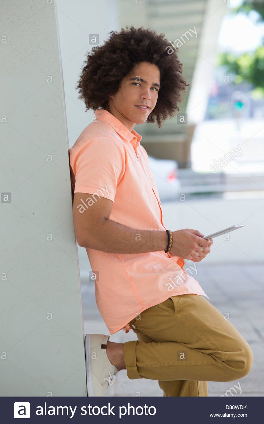 Portrait of smiling young man using digital tablet and leaning against wall - Stock Image