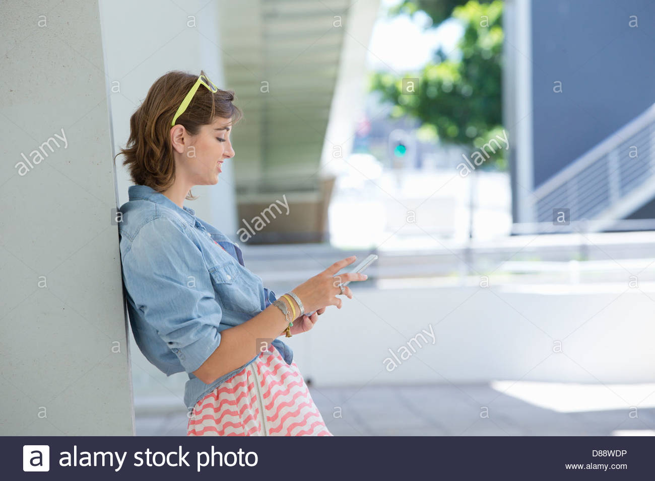 Young woman using digital tablet and leaning against wall - Stock Image