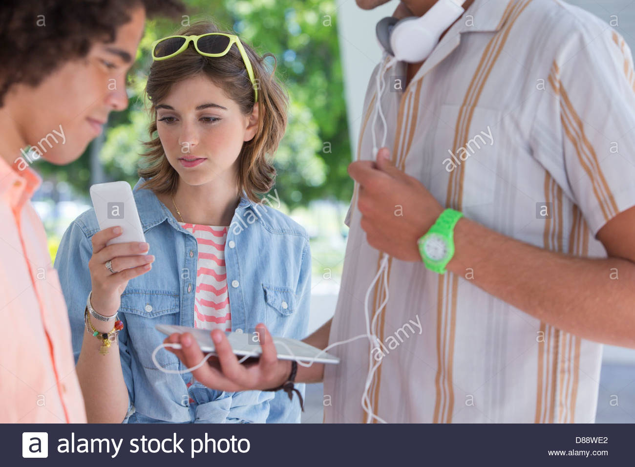 Friends using cell phone and digital tablet - Stock Image