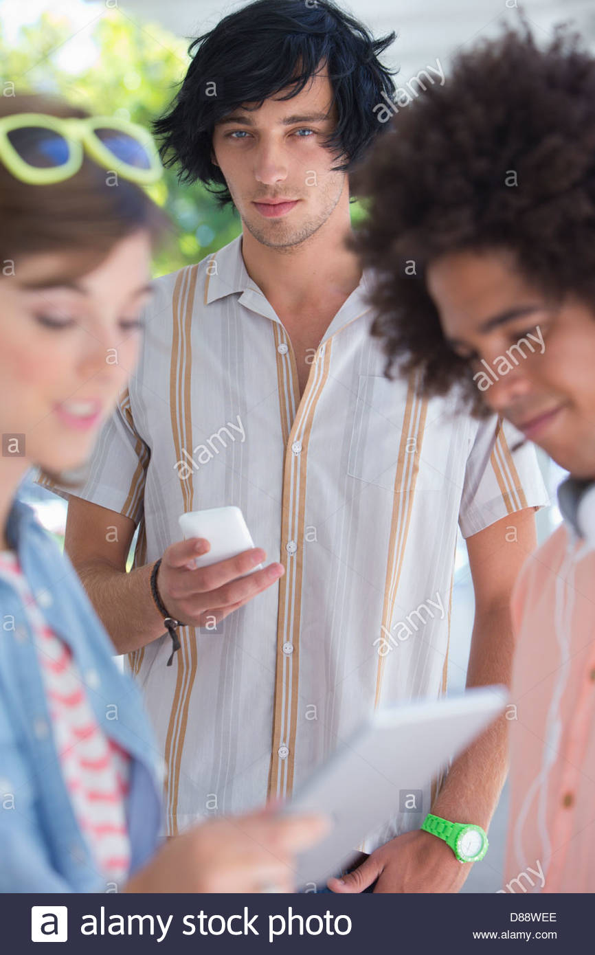 Portrait of friends using cell phone and digital tablet - Stock Image