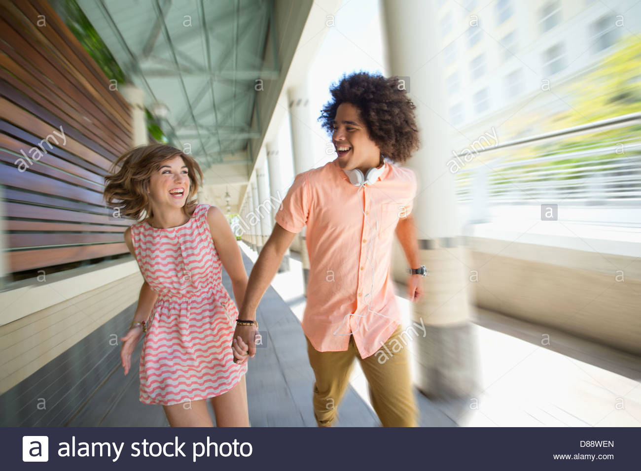 Enthusiastic young couple running along corridor - Stock Image