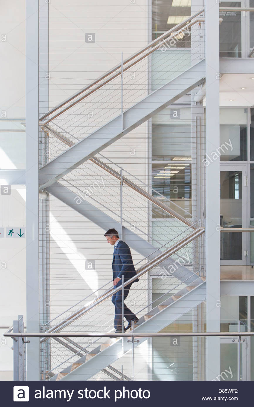 Businessman descending stairs in office - Stock Image